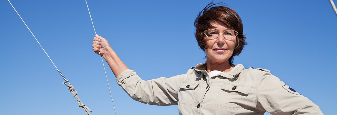 woman yachtsman on a sailing yacht holds on to the ropes at sunny day