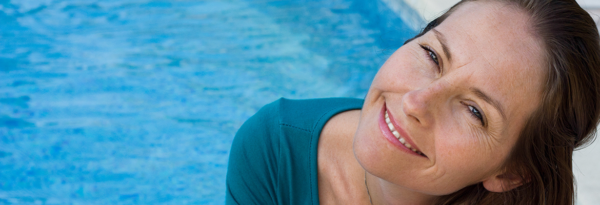 woman by a pool looking happy but a little suspicious