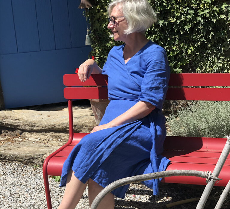 Bright blue summer dress on a bright red bench